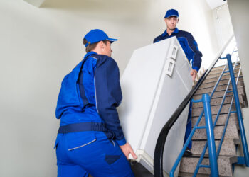 Movers taking a refrigerator upstairs